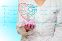 Concept of health and medicine - female doctor holding a red heart with gears with ecg lines. Concept of health and medicine female doctor holding a red heart stock photos