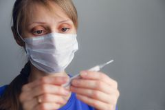 The concept of health. A sick girl with a fever in a disposable medical mask looks at the thermometer. Shut. The girl checks the stock photography