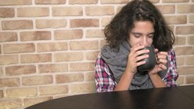 The concept of seasonal fever. Sick teenager boy holding a cup of hot drink. Unhappy teenager with curly brunette hair. The concept of healthcare and medicine stock video