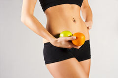 Concept of a healthy body. Thin belly, fruit Royalty Free Stock Photos
