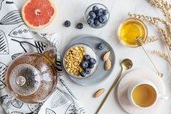 Concept of healthy breakfast. Oatmeal with nuts, berries and milk, honey, grapefruit and tea stock photos