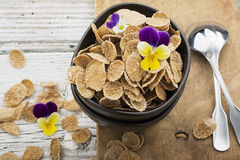 The concept of a healthy breakfast: whole-grain flakes with edible garden flowers, berries in dark ceramic bowls on a Royalty Free Stock Photography