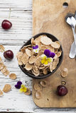 The concept of a healthy breakfast: whole-grain flakes with edible garden flowers, berries in dark ceramic bowls on a Royalty Free Stock Images