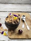 The concept of a healthy breakfast: whole-grain flakes with edible garden flowers, berries in dark ceramic bowls on a Stock Photo