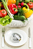 Concept of a healthy diet. The basket of vegetables and a plate. With measuring tape Stock Photo