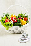 Concept of a healthy diet. The basket of vegetables, and scales. With measuring tape Royalty Free Stock Photography