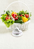 Concept of a healthy diet. The basket of vegetables, and scales. With measuring tape Stock Images