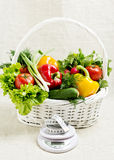 Concept of a healthy diet. The basket of vegetables, and scales. With measuring tape Royalty Free Stock Photo