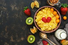 The concept of healthy eating. Cornflakes, milk, strawberries, kiwi, almonds. A delicious healthy Breakfast. Top view, copy space. The concept of healthy eating Stock Image