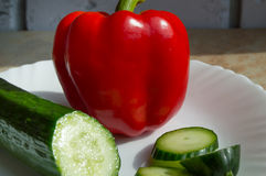 Concept of healthy eating, sliced cucumber and pepper on white plate.  Stock Images