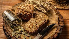The concept of healthy eating. Whole grain bread with seeds of goji berry, pumpkin, on a plate on a wooden background. Concept of healthy eating. Whole grain stock photography