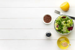 Concept of healthy food. Fresh salad in bowl with flax seed on white wooden table. Stock Photo