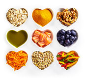 Concept of healthy food for the heart. And cardiovascular system with heart-shaped dishes containing oats, turmeric, walnuts, salmon, acai, carrot, lentils Royalty Free Stock Images