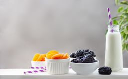 Concept healthy food, vegetarianism, diet. Yogurt, dried apricots and prunes in a white bowls stock photos