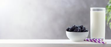 Concept healthy food, vegetarianism, diet. A glass of yogurt and prunes. Bright background with copy space stock photo
