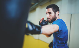 Concept of a healthy lifestyle.Bearded muscular man fighter practicing kicks with punching black bag.Kick boxer boxing Stock Image