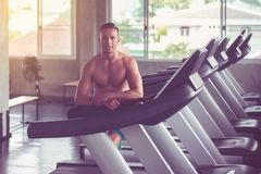 Concept healthy and lifestyle,Fit man relax after the training session in gym,Male taking a break after exercise and workout royalty free stock images