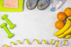 The concept of a healthy lifestyle and sport, against the background of running shoes, dumbbells and towels, bananas and oranges, royalty free stock image