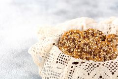 Concept of healthy nutrition: fitness cookies with sesame seeds in a wicker napkin plate. Light background stock images