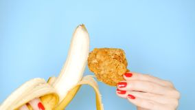 Concept of healthy and unhealthy food. banana against fried breaded chicken leg on a bright blue background. female royalty free stock image