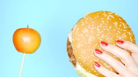 Concept of healthy and unhealthy food. Yaloko against hamburgers on a bright blue background. female hands with red nail stock footage