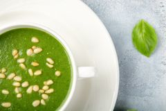 The concept of a healthy, vegetarian or dietary food: cream spinach soup, with pine nuts and basil. With slices of vegetarian. Carrot bread. On a light stock image