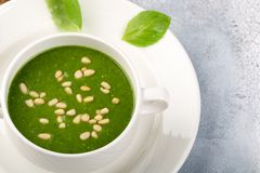 The concept of a healthy, vegetarian or dietary food: cream spinach soup, with pine nuts and basil. With slices of vegetarian. Carrot bread. On a light royalty free stock photos