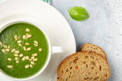 The concept of a healthy, vegetarian or dietary food: cream spinach soup, with pine nuts and basil. With slices of vegetarian royalty free stock photos
