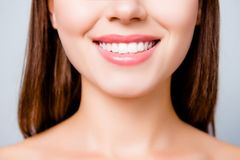 Concept of healthy wide beautiful smile. Cropped close up photo. Of healthy without caries shiny toothy woman`s smile, isolated on grey background Stock Images