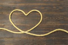 Concept of heart of the jute ropes, love, frame for greeting card on brown wooden background stock photo