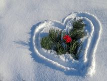 Heart drawn in the snow. Branches of cedar and viburnum berries royalty free stock photos