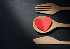 Concept, A heart is in a wooden spoon, fork and knife like some. Concept of Valentine's, A red paper heart is in a wooden spoon, fork and knife like some food on stock images