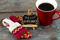Concept HELLO january message on blackboard with a Cup of coffee. And mittens Stock Photos