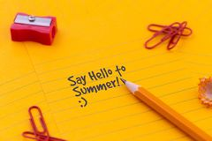 Concept Hello summer or planning a summer trip. Orange sheets of paper, pencil and other stationery objects.  stock image