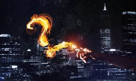 Concept of help or support with fire burning question mark against night city background. Burning fire question mark or sign on dark background royalty free stock photo