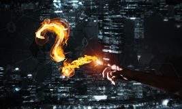 Concept of help or support with fire burning question mark against night city background. Burning fire question mark or sign on dark background stock photo