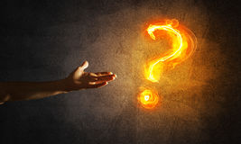 Concept of help or support with fire burning question mark and creation gesture. Close of man hand showing burning fire sign on dark background Stock Image