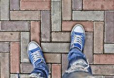 Concept: Het begin van de weg, de keus van richting Mening van hierboven Benen in blauwe tennisschoenen op de bestrating De keus, stock afbeeldingen