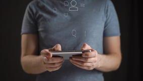 Concept, het digitale online leven en sociale netwerken Een jonge mens in een blauwe T-shirt gebruikt zijn smartphone om zijn rek stock footage