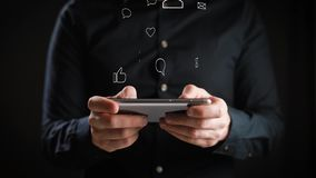 Concept, het digitale online leven en sociale netwerken Een jonge mens in een overhemd gebruikt zijn smartphone om zijn rekeninge stock videobeelden