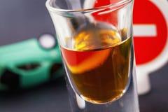 Concept het drijven terwijl bedwelmd Een glas whisky met een omgekeerde machine en verkeersteken is belemmerd van het binnengaan royalty-vrije stock foto