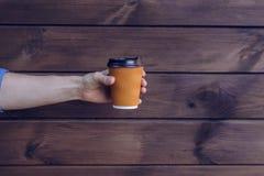 Concept het hebben van verse kop van koffie in de ochtend De holdingskop van de mensen` s hand van koffie tegen bruine houten ach royalty-vrije stock afbeeldingen