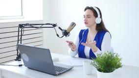 Concept het stromen en het uitzenden Het jonge vrolijke meisje in de studio spreekt in een microfoon stock video
