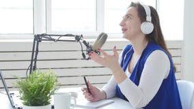 Concept het stromen en het uitzenden Jonge vrouw die hoofdtelefoons dragen en bij online radiostation spreken stock videobeelden