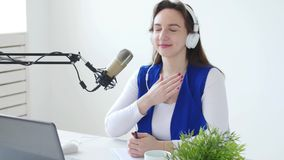 Concept het stromen en het uitzenden Jonge vrouw die hoofdtelefoons dragen en bij online radiostation spreken stock footage