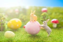 Concept heureux de Pâques Peu de jouets de lapin de Pâques et oeufs de pâques sur l'herbe verte Coucher du soleil de conte de fée Photos stock