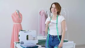 Concept of hobby and small business. Beautiful young female tailor smiling at camera. In studio stock footage