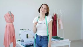 Concept of hobby and small business. Beautiful young female tailor smiling at camera. In studio stock video