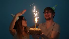 Concept of holiday and birthday. Young cheerful funny couple having fun with birthday cake