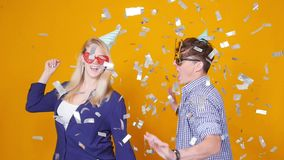 Concept of holiday and birthday. Young happy couple dancing in hats on orange background with confetti stock footage
